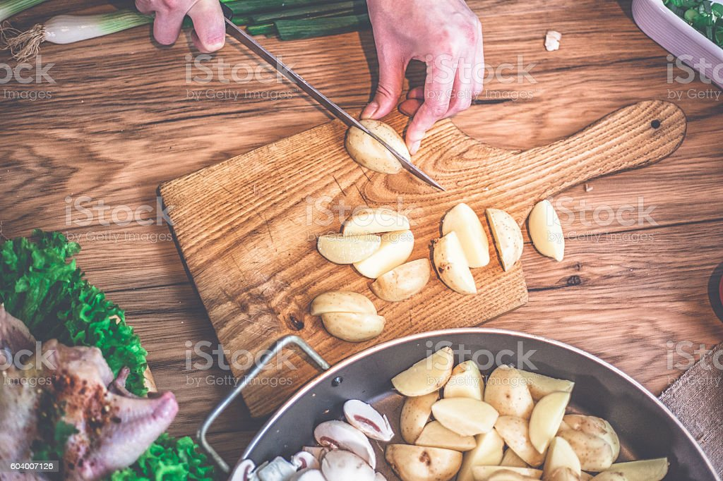 Female hands cutting potatoes on wooden board. stock photo