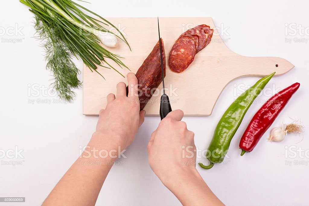 Female hands cutting slices of red sausage stock photo