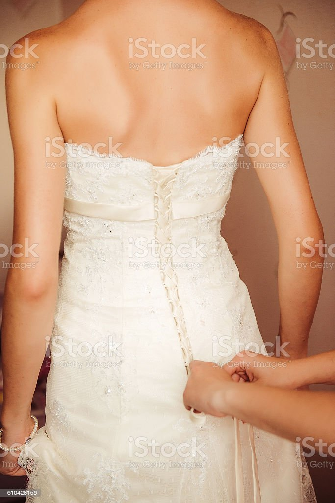 Female hands fastening buttons on a wedding dress stock photo