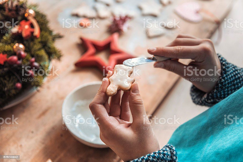female hands finishing christmas cookie at wooden table stock photo