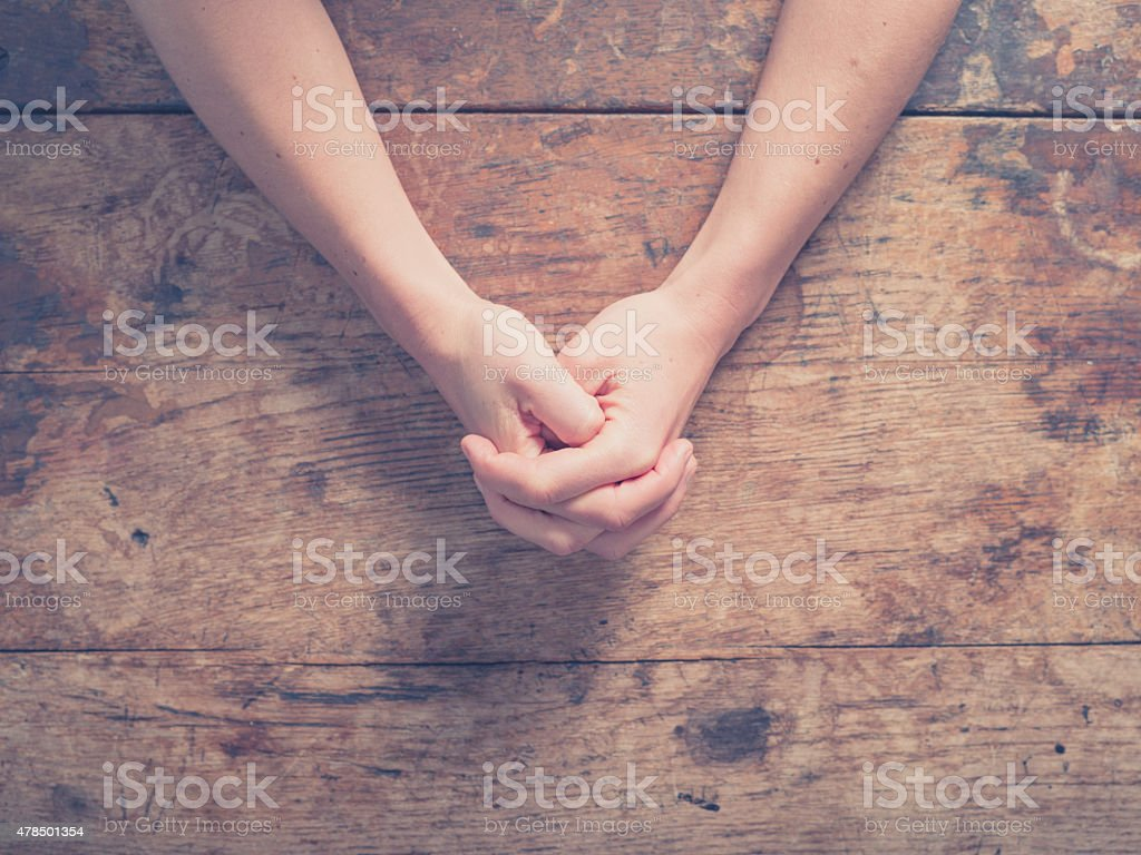 Female hands folded at table stock photo