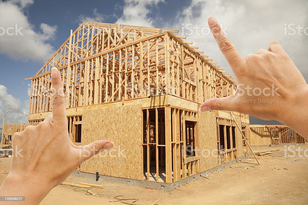 Female Hands Framing Home Frame on Construction Site stock photo