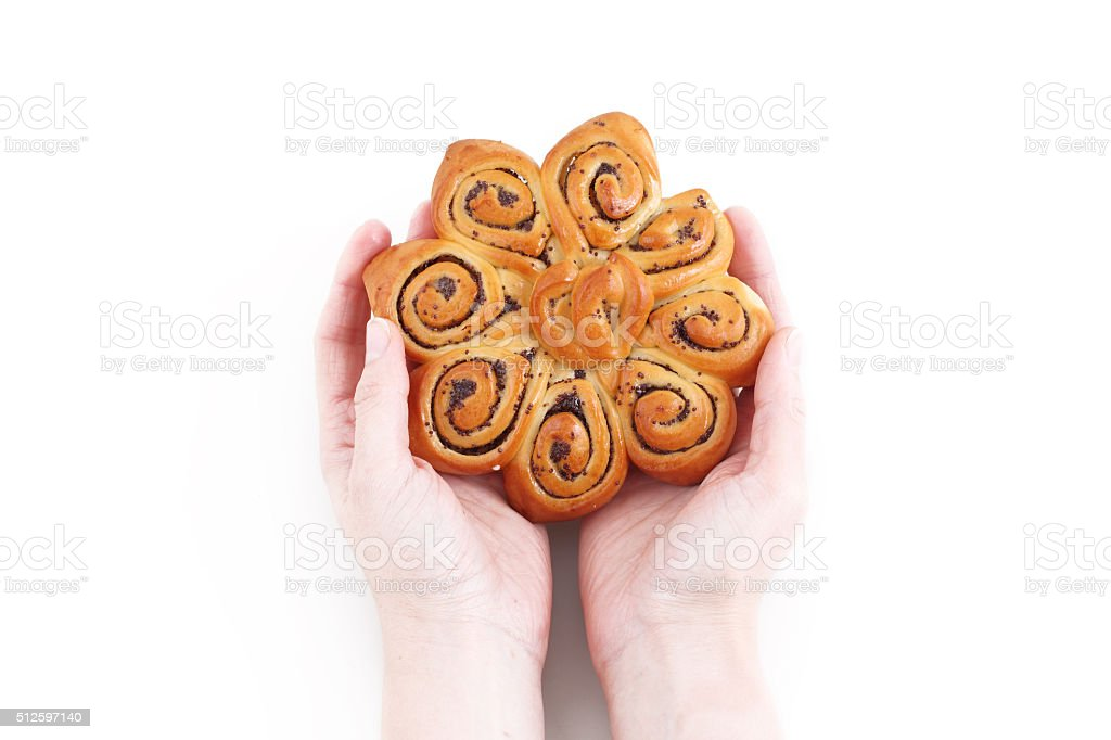 Female hands hold a bun with a poppy stock photo