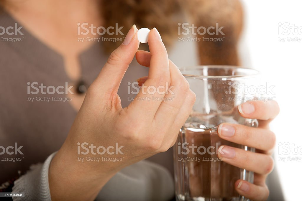 Female hands hold pill and glass of water stock photo