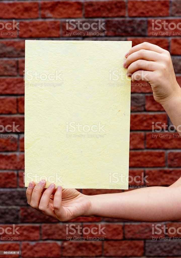Female hands hold sheet of cream, textured paper against brick stock photo