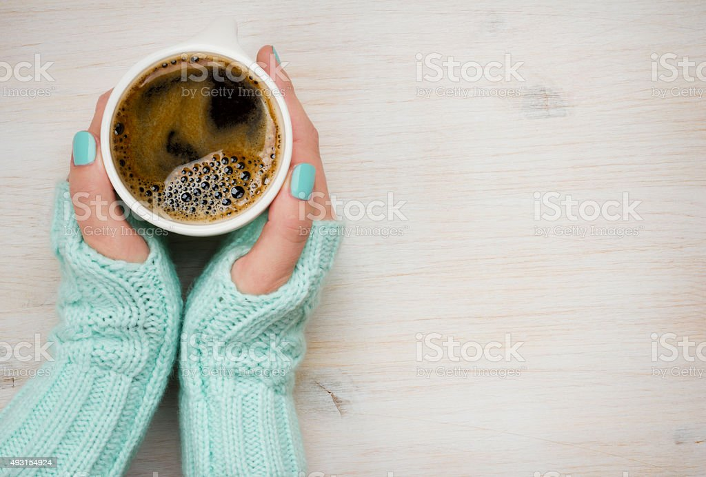 Female hands holding a coffee mug in knitted mittens stock photo