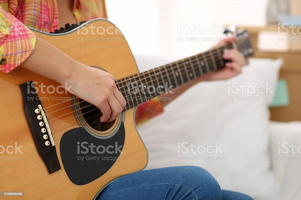 Female hands holding and playing western acoustic guitar closeup stock photo