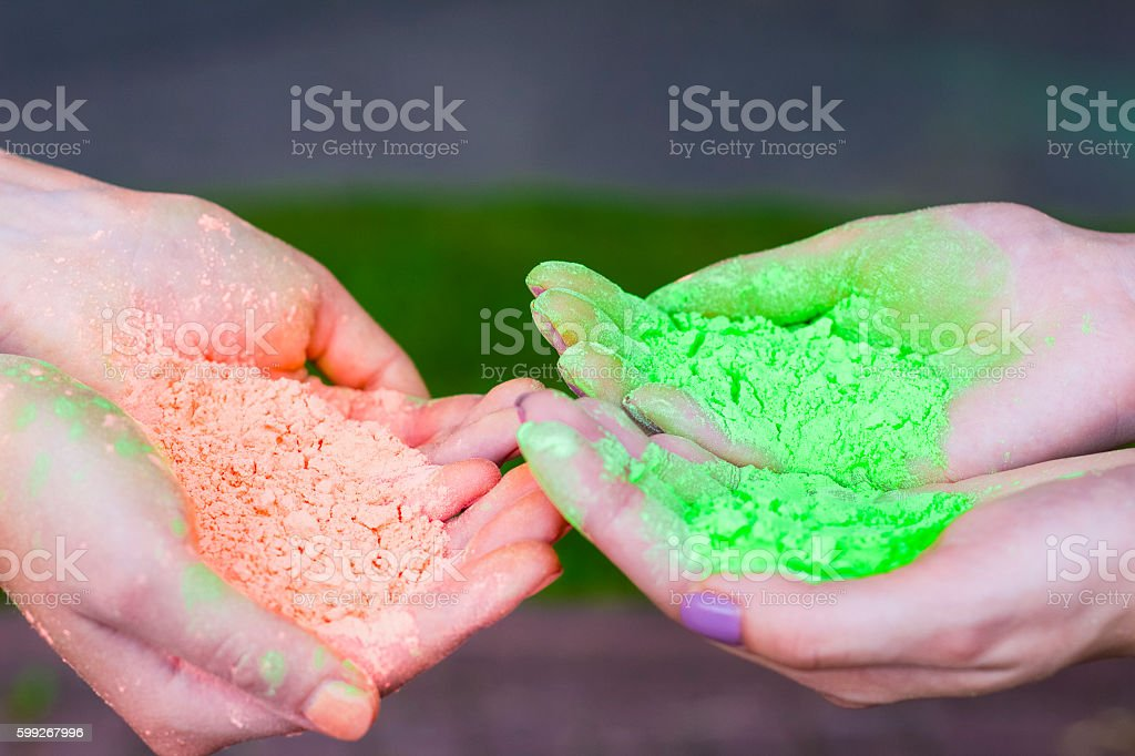 Female hands holding  color powder stock photo