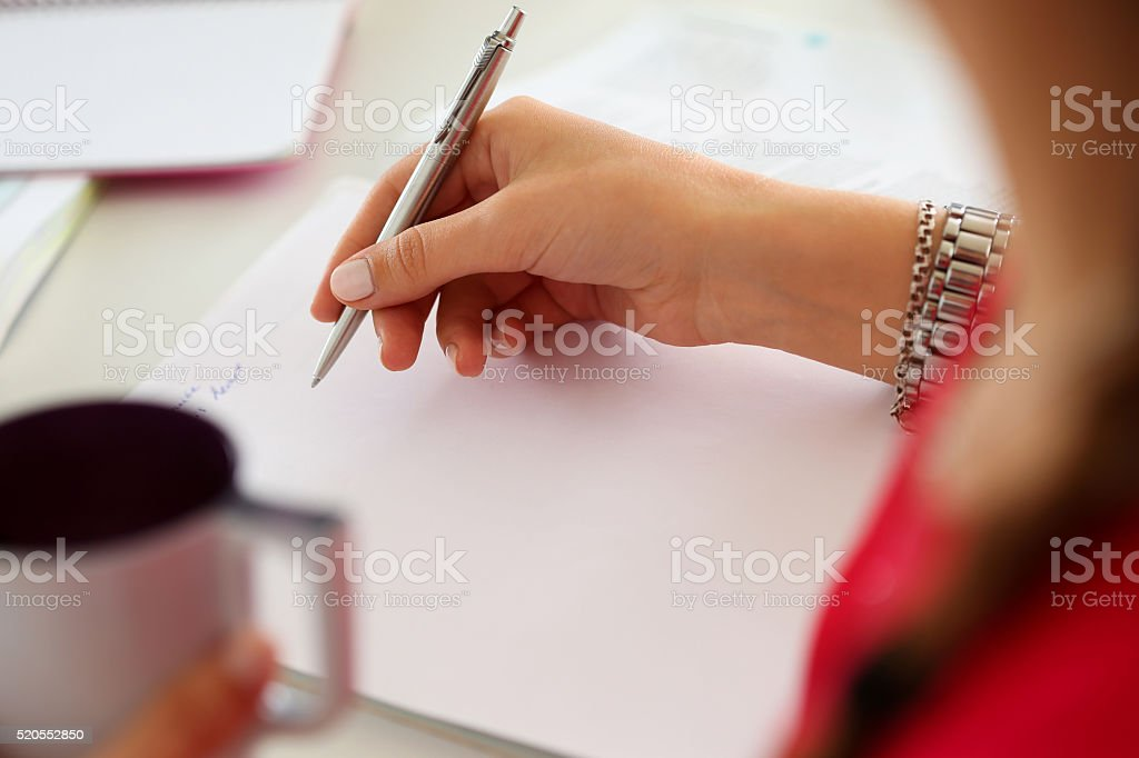 Female hands holding cup of coffee or tea and pen stock photo