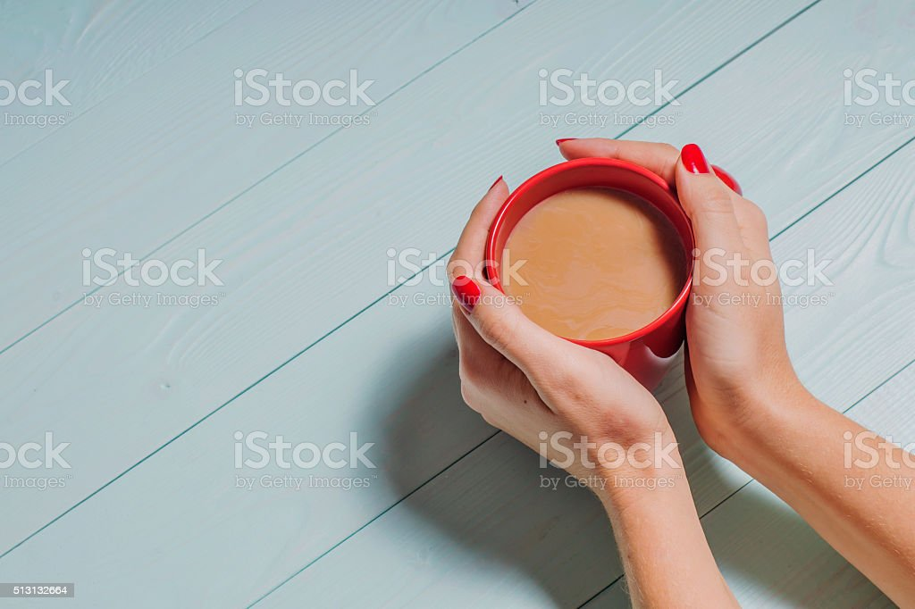 Female hands holding cups of coffee over wooden  background, stock photo