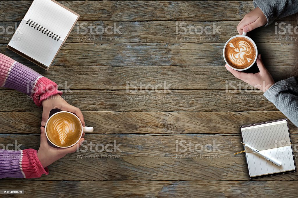 Female hands holding cups of latte art coffee stock photo