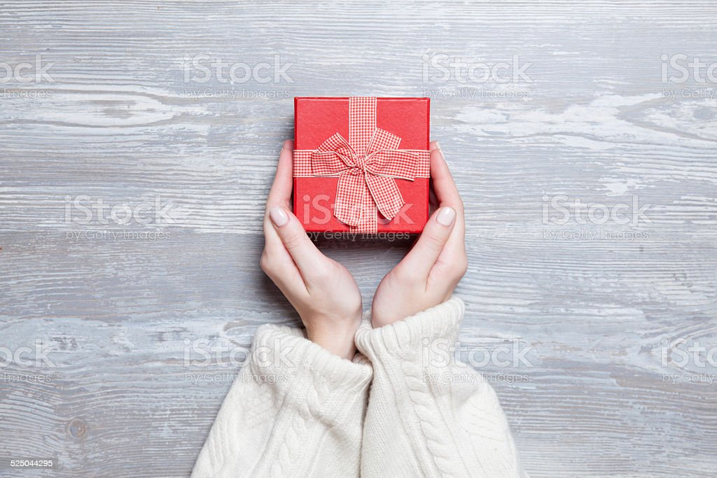 Female hands holding gift on wooden table. stock photo