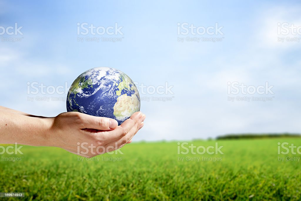 Female hands holding planet earth in rural scene royalty-free stock photo