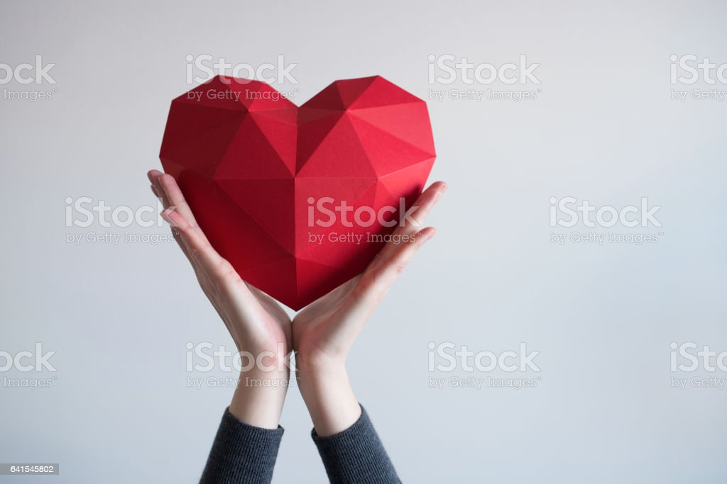 Female hands holding red polygonal heart shape stock photo