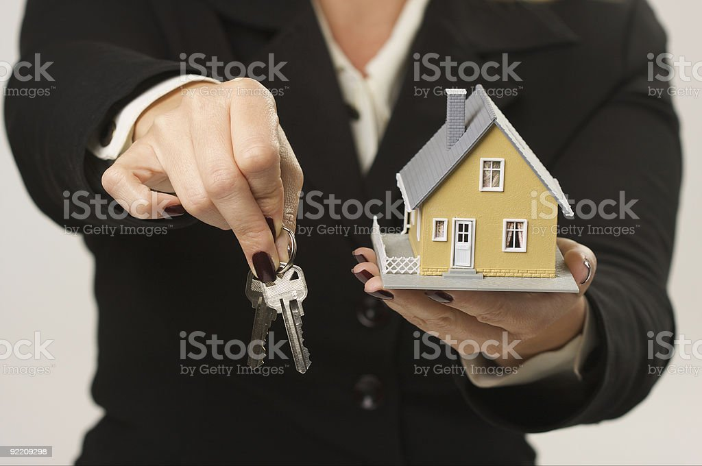 Female Hands Holding Small House and Keys royalty-free stock photo