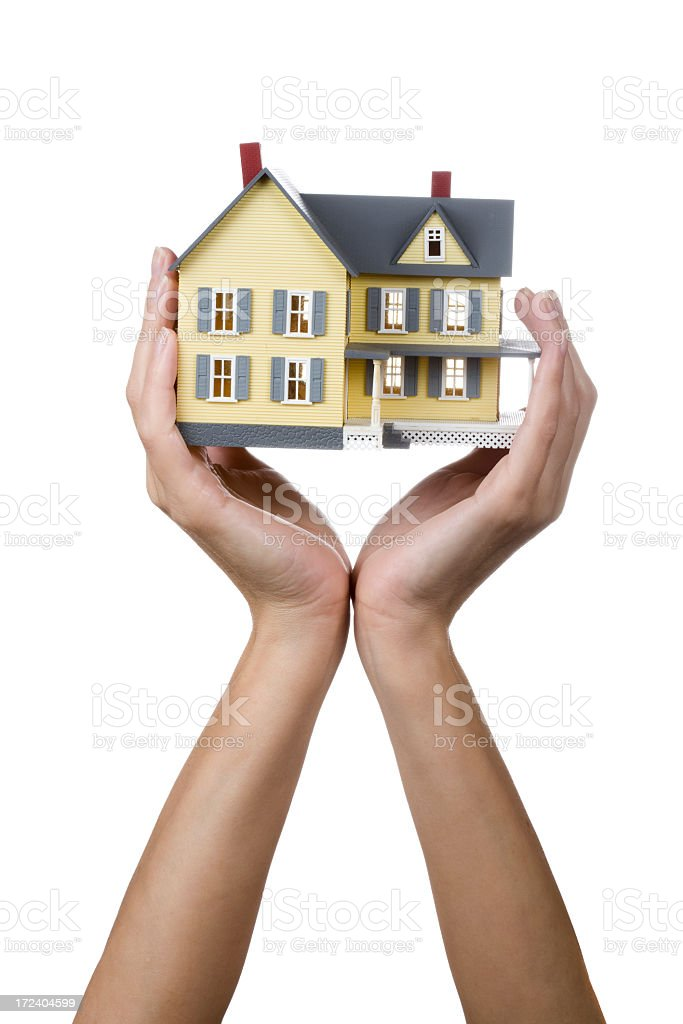 Female hands holding up a yellow model house stock photo