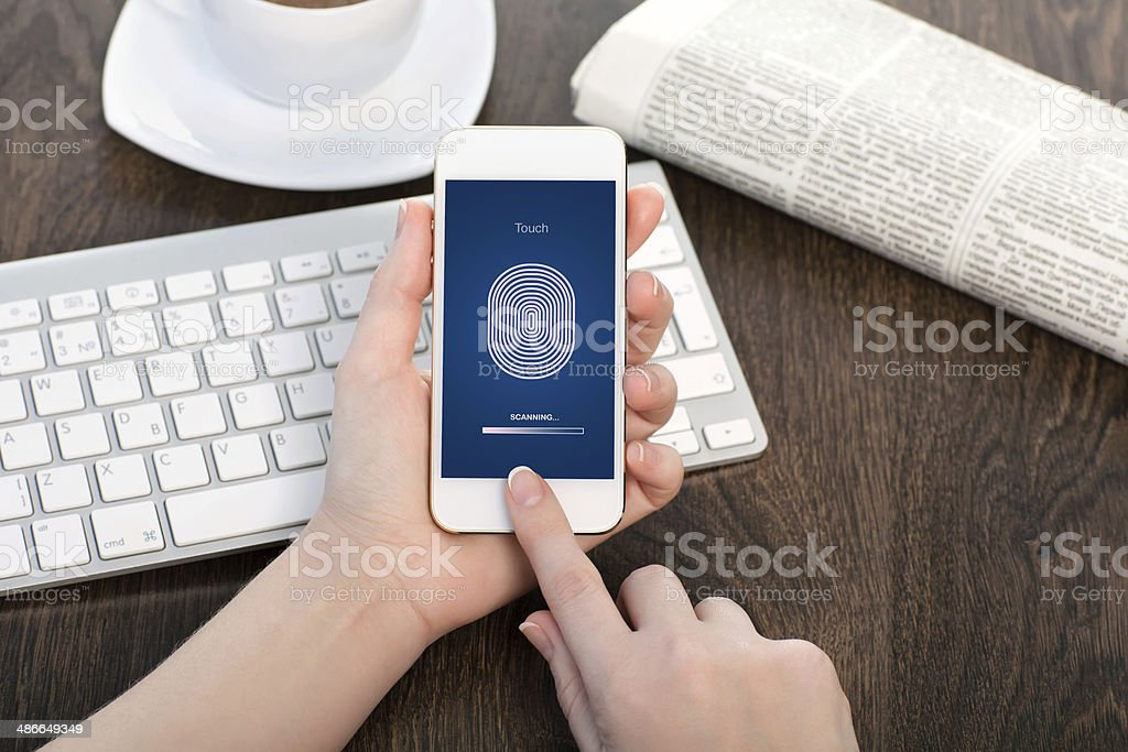 female hands holding white touch phone and entering PIN code stock photo