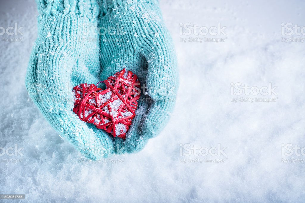 Female hands in teal knitted mittens stock photo