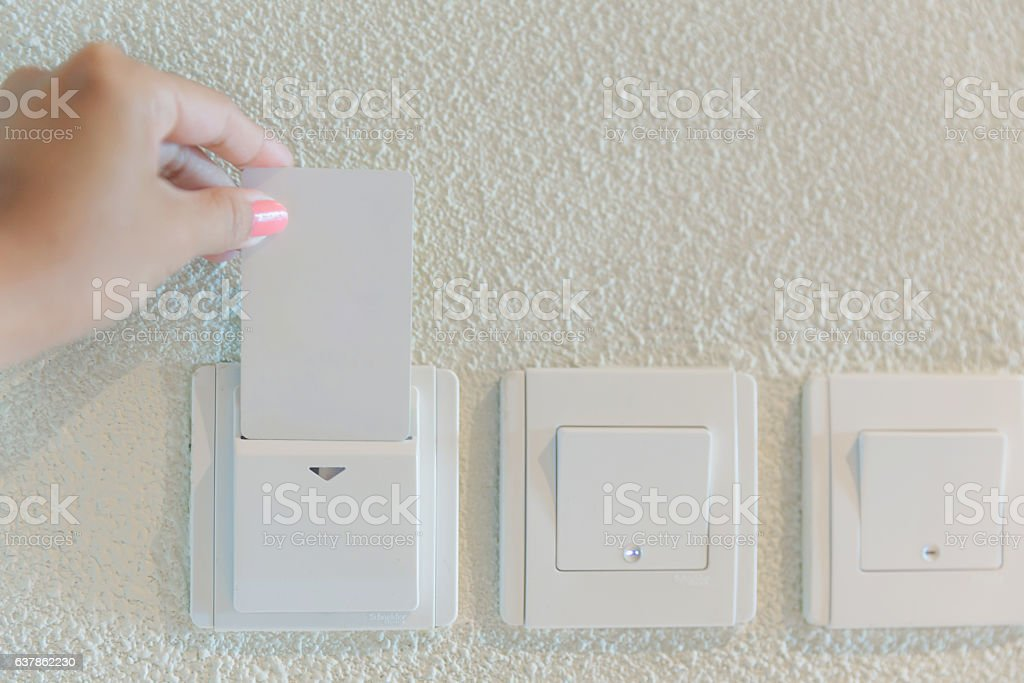 Female hands inserting hotel cardkey for lights stock photo