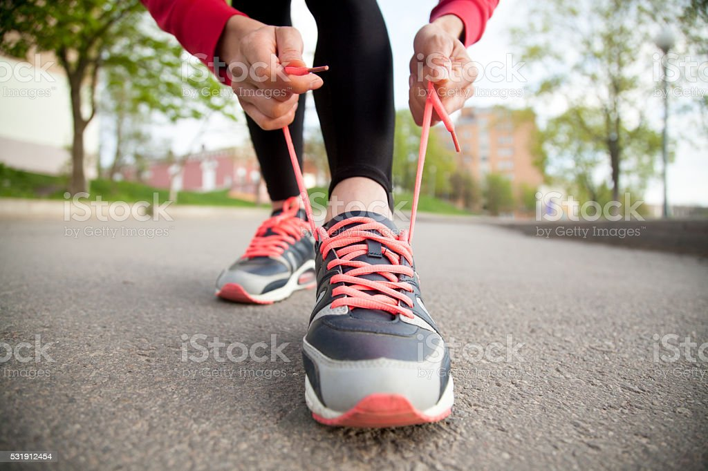 Female hands lacing running shoes. Closeup stock photo