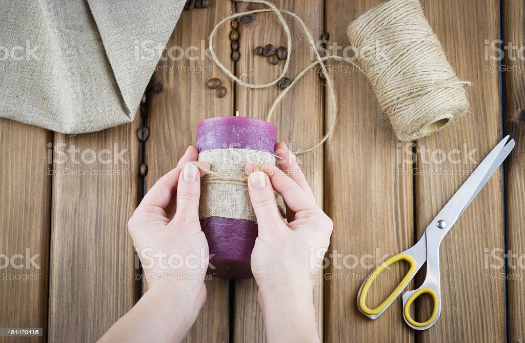 Female hands make candle decorated with sackcloth and twine stock photo