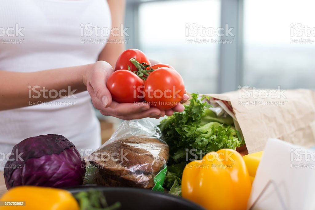 Female hands of a caucasian cook holding red tomato bunch stock photo