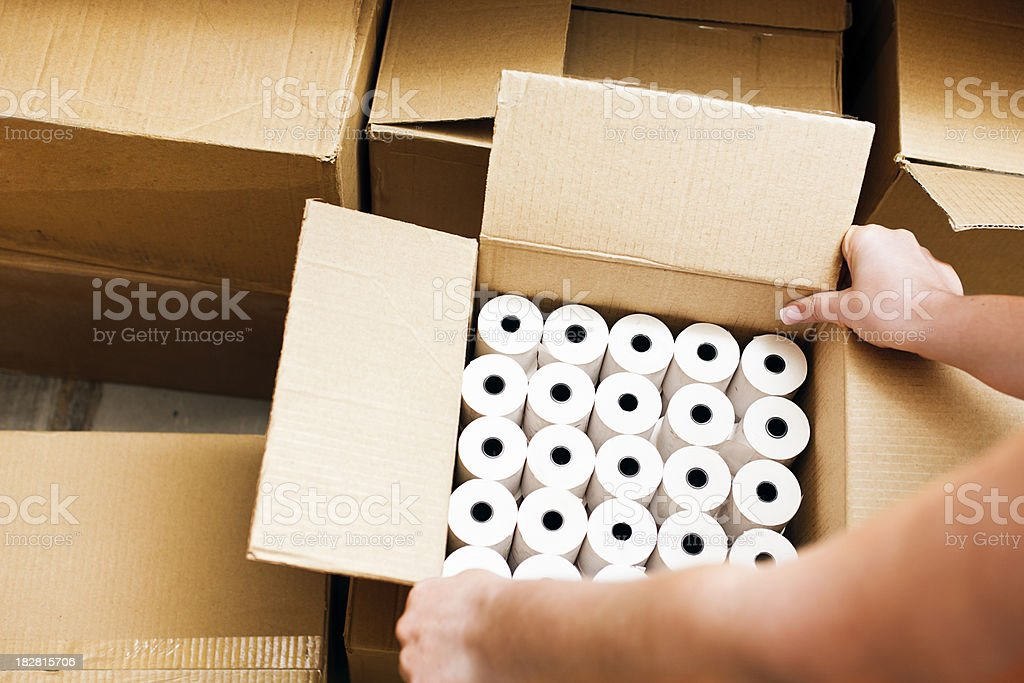 Female hands open box of paper rolls stock photo