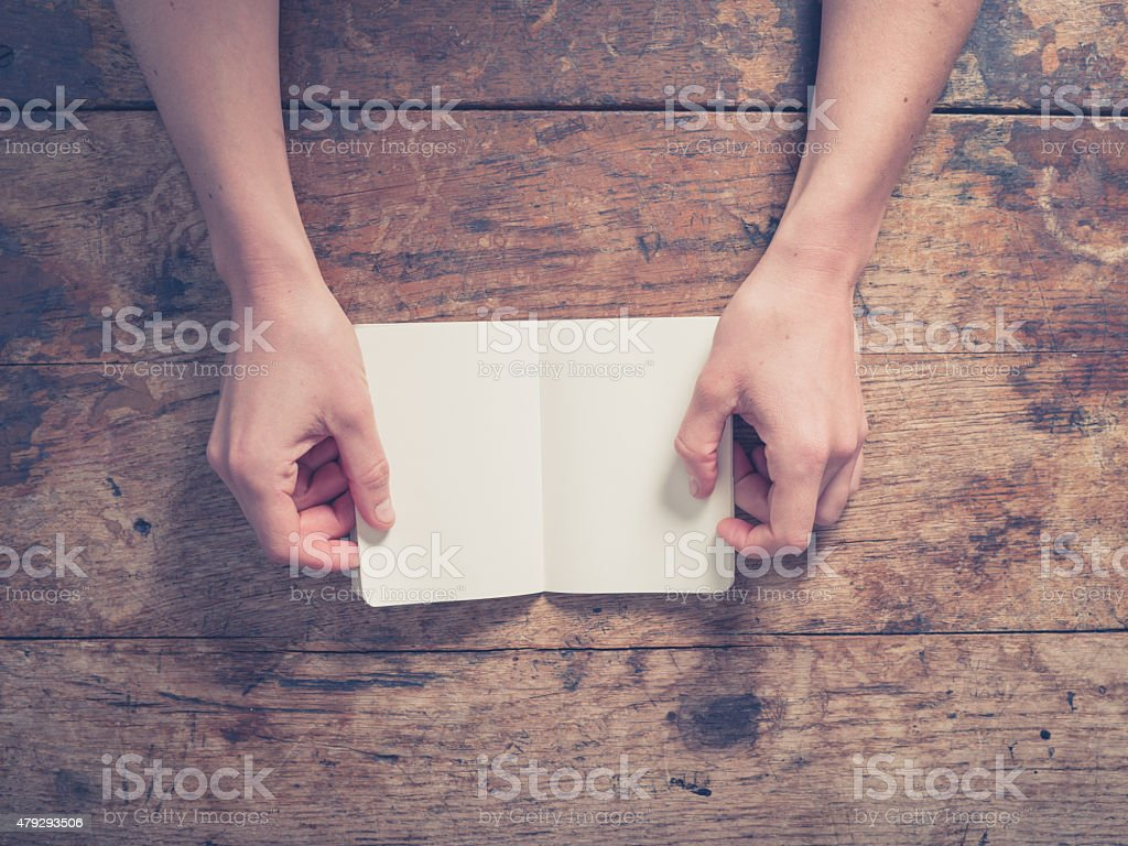 Female hands opening small notepad stock photo