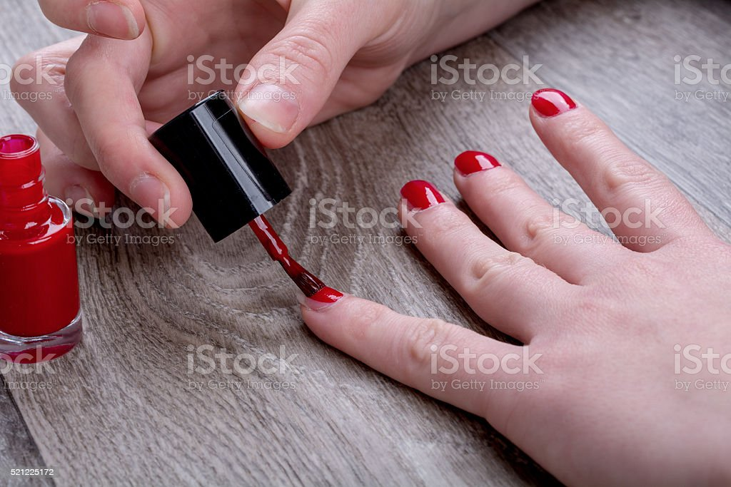 Female hands painting red nail varnish stock photo