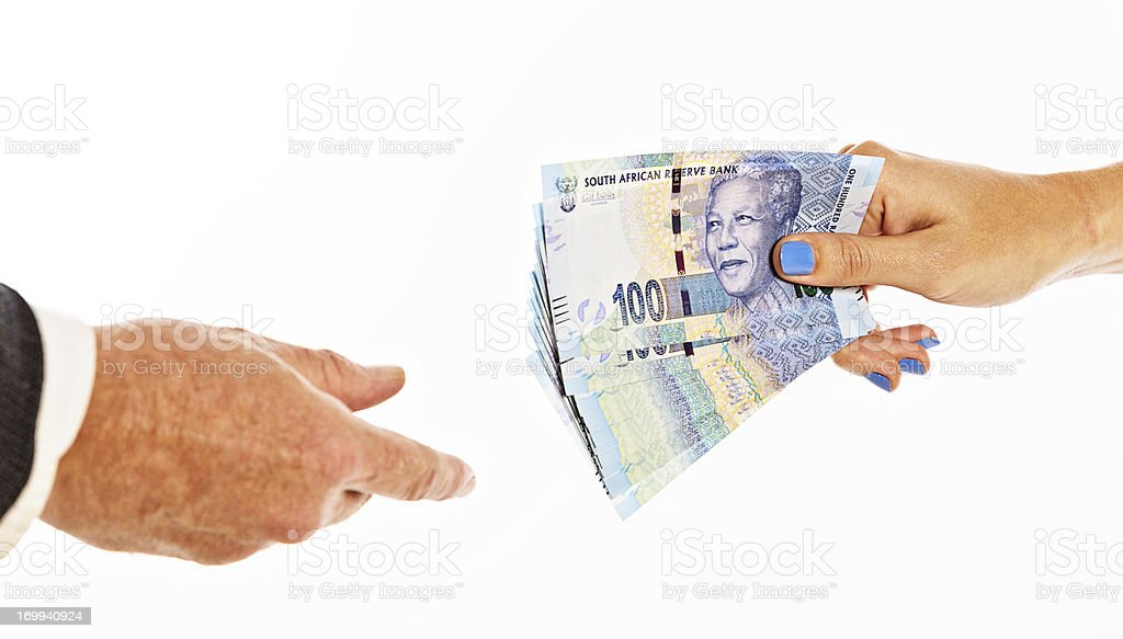 Female hands passing bundle of hundred-rand notes to man royalty-free stock photo