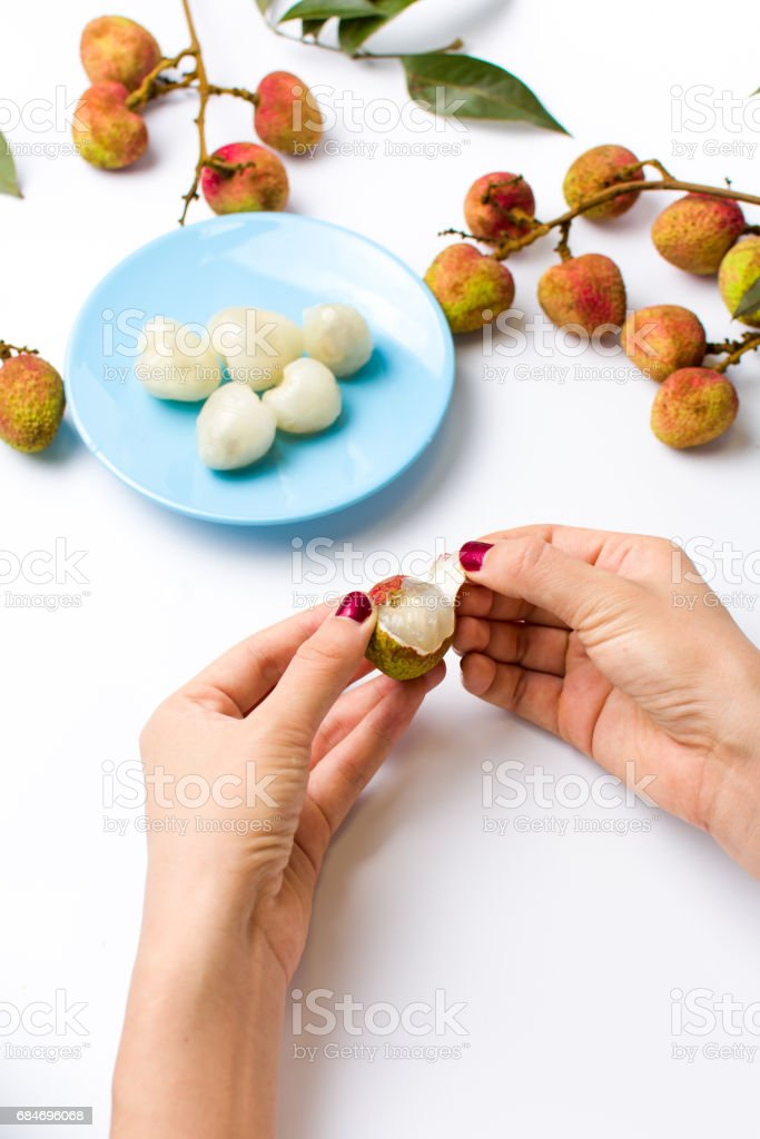 Female hands peeling lychee fruit stock photo