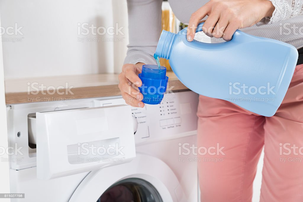 Female Hands Pouring Detergent In The Bottle Cap stock photo