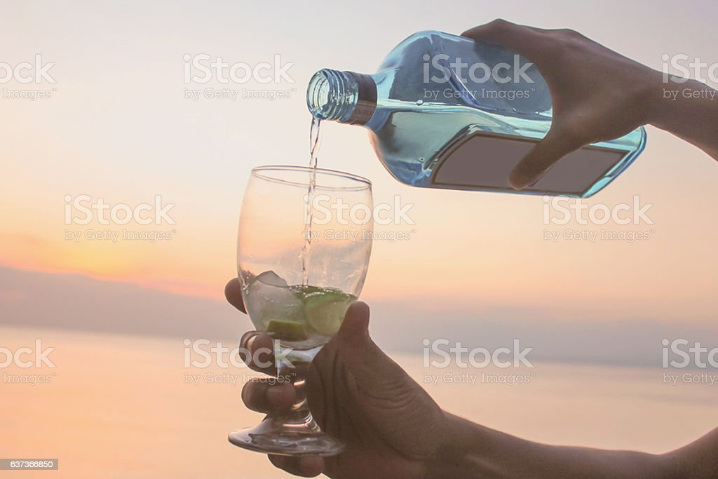 Female hands pouring gin to glass with sunset backgrounds stock photo