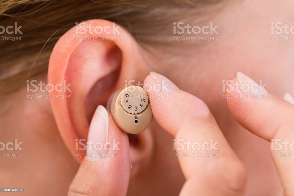 Female Hands Putting Hearing Aid In Ear stock photo