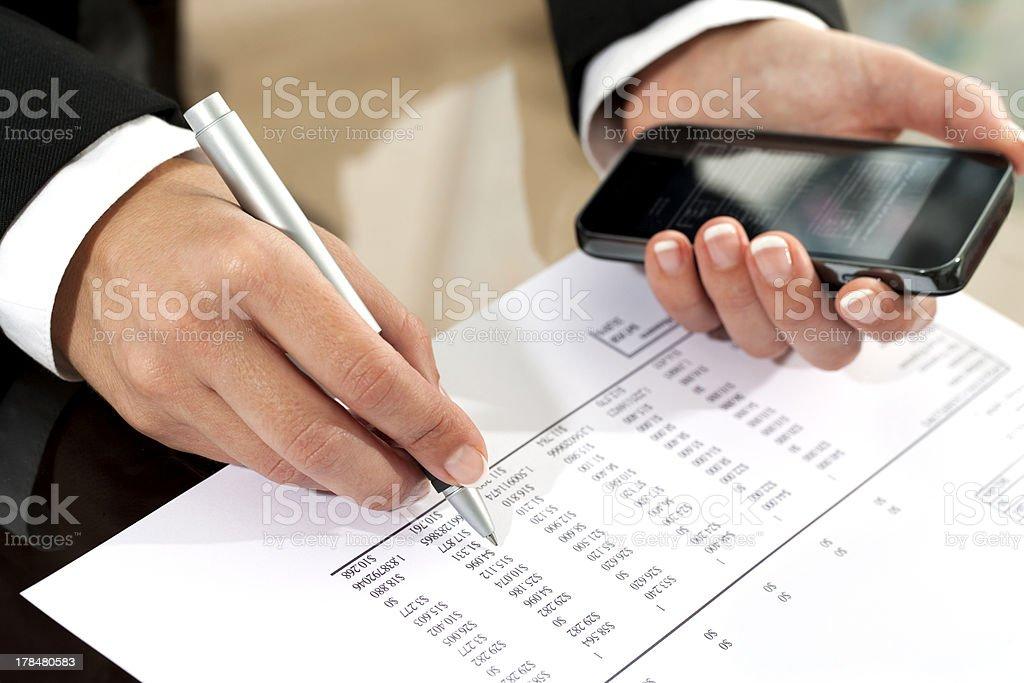 Femme main examinant un document de comptabilité. photo libre de droits