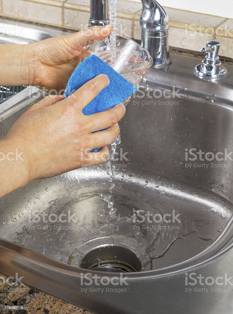 Female hands running water into Soapy Drinking Glass royalty-free stock photo