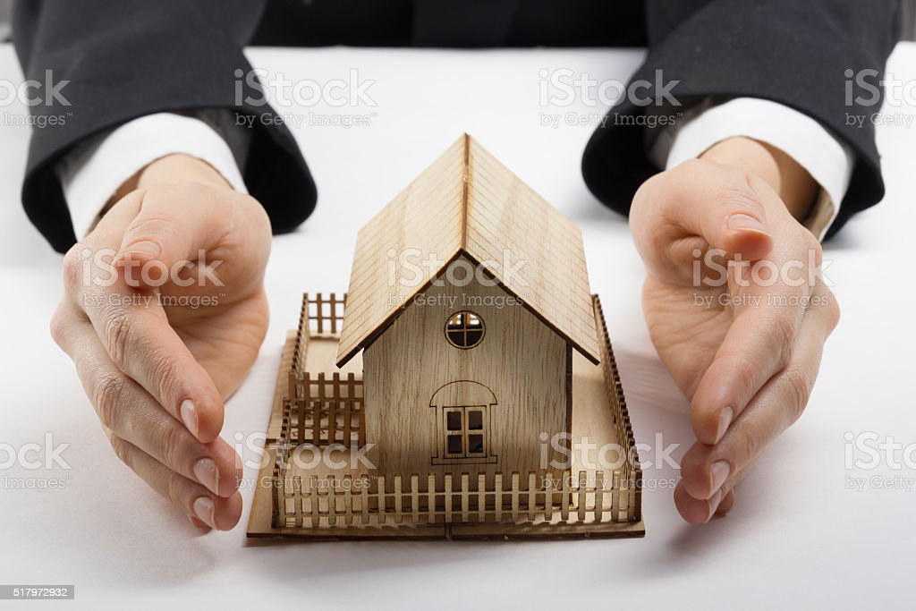 Female hands saving small house with a roof stock photo