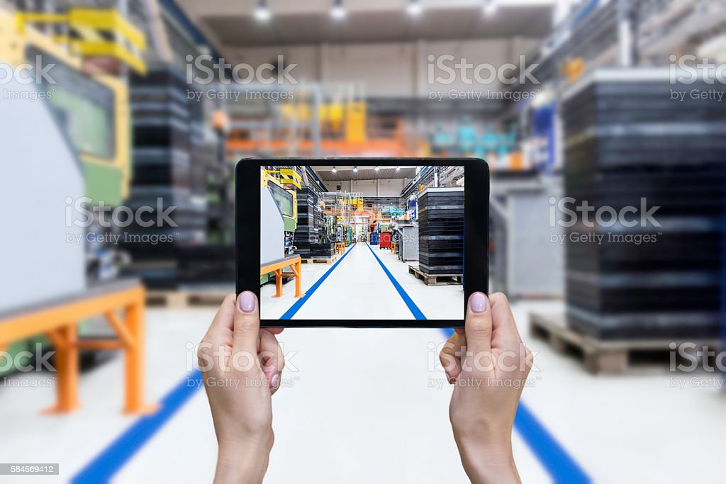 Female hands showing factory on tablet stock photo