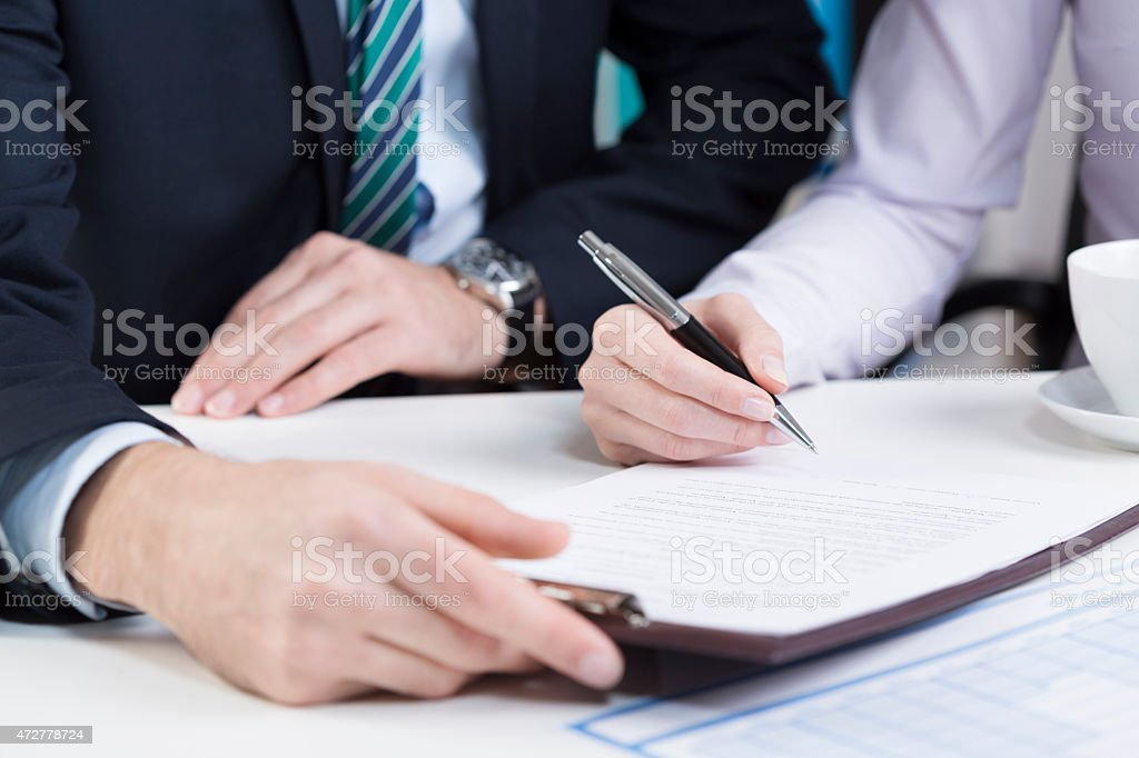 Female hands signing contract stock photo