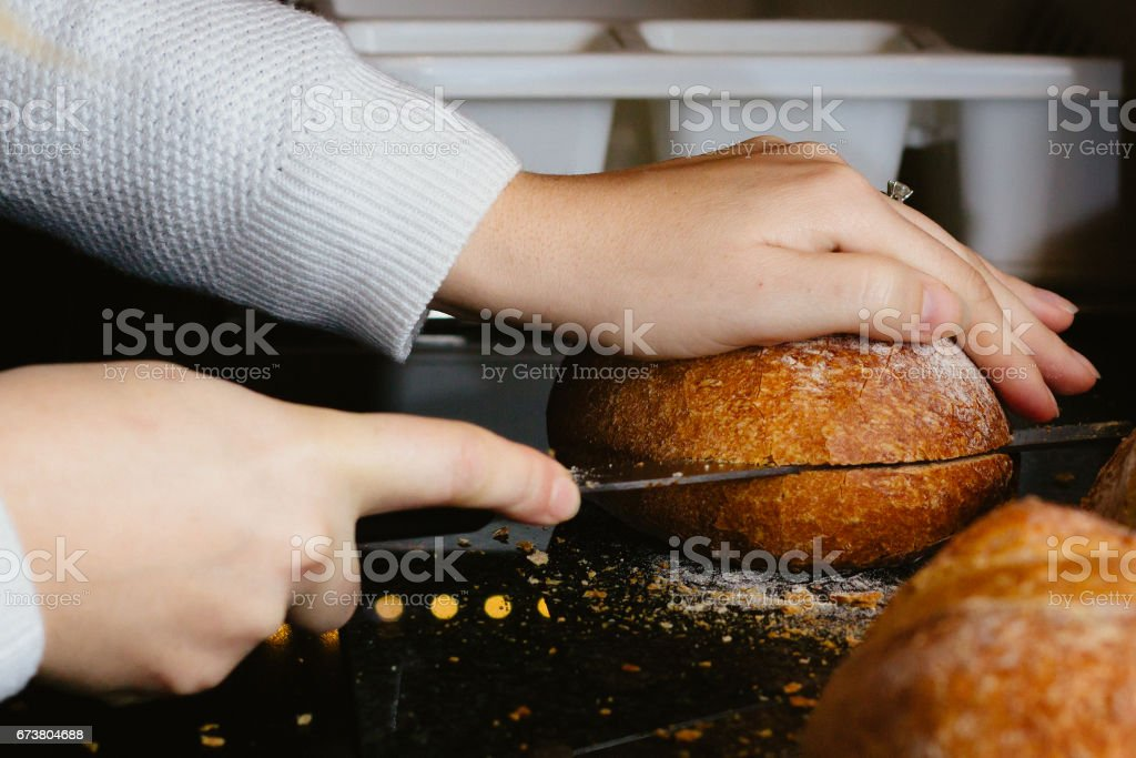Female hands slicing fresh bread with a large knife on a reflective kitchen counter stock photo