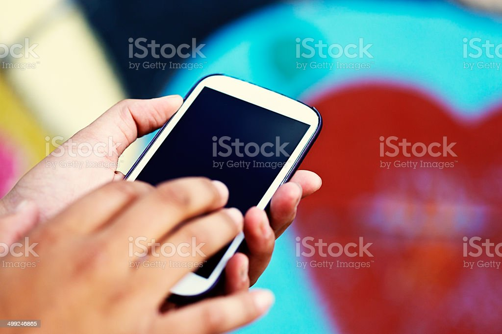 Female hands tap cellphone screen, heart shape in background stock photo