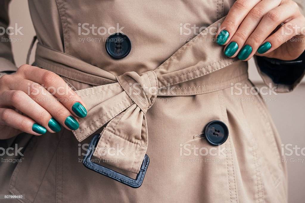 Female hands tie belt on a coat stock photo