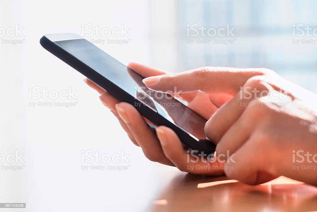 Female hands touching and using cell in sun filled room stock photo