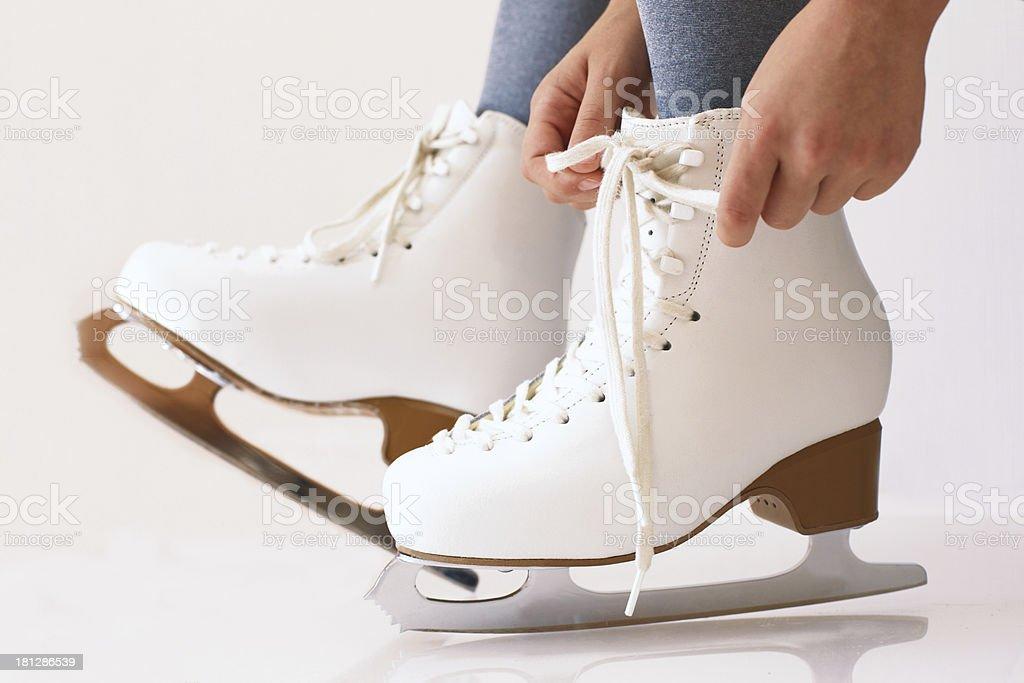 Female hands tying white ice skates royalty-free stock photo