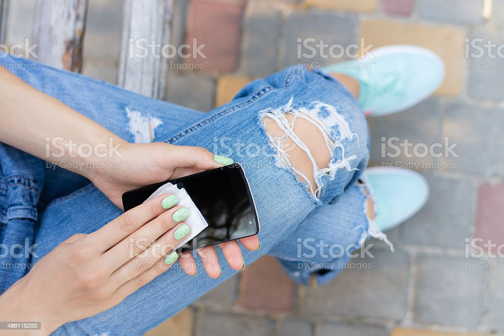 Female hands wipe the touch screen phone antibacterial wipes stock photo