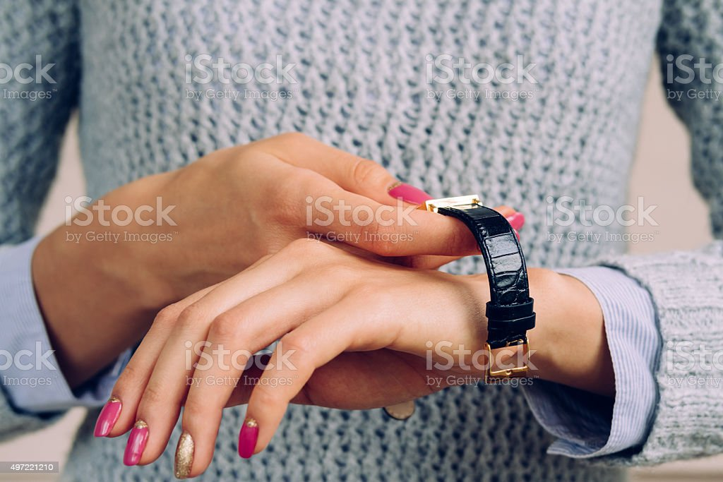 Female hands with a bright manicure dress watch on wrist stock photo
