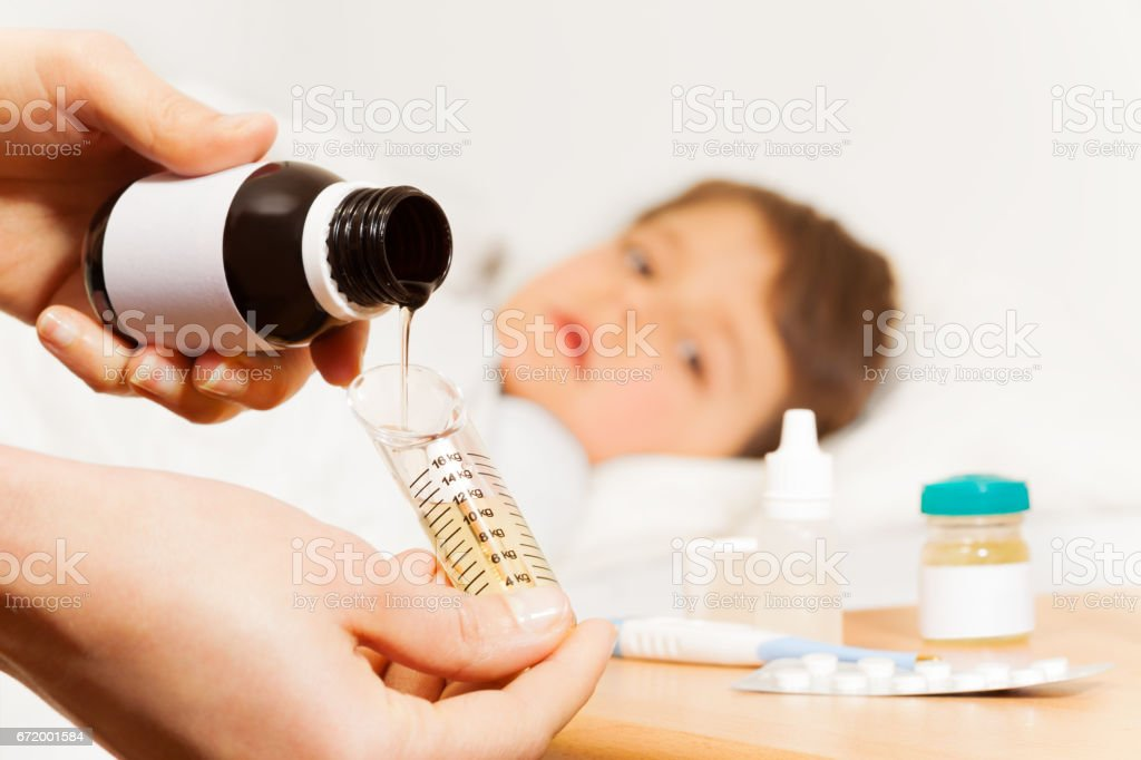 Female hands with antipyretic syrup for sick boy stock photo