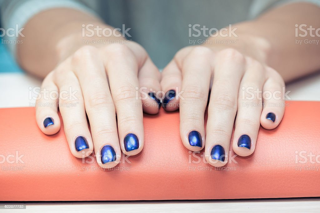 female hands with  blue nail Polish, close-up stock photo