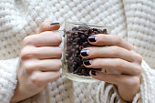 Female hands with dark brown nail design.