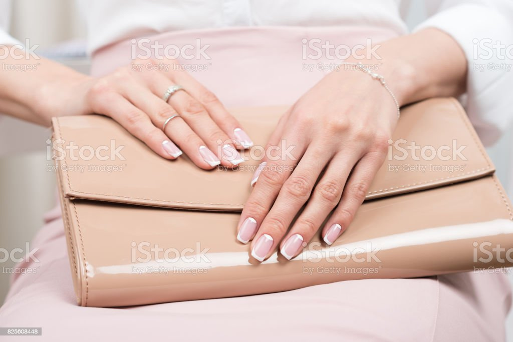 female hands with french manicure holding leather bag stock photo